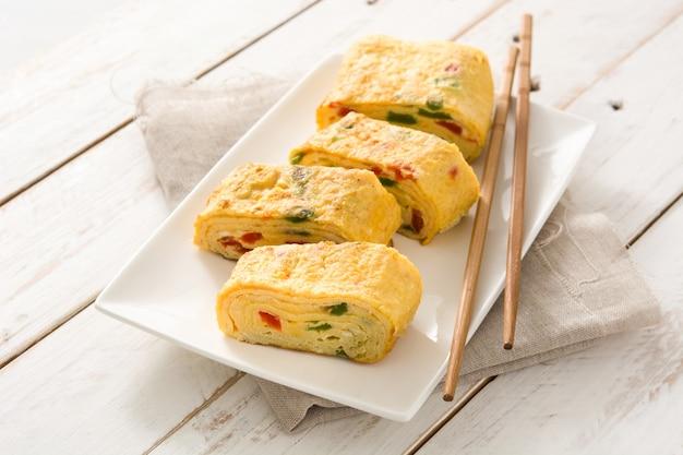 Traditional tamagoyaki japanese omelette on white wooden table.