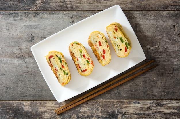 Traditional tamagoyaki japanese omelette on wooden table