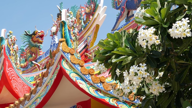 Traditional taoist chinese temple roof decoration. asian religious monastery in bloom of flowers.