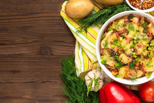 나무 테이블 위에 베이컨, 허브, 야채와 전통적인 tartiflette. 공간을 복사하십시오.