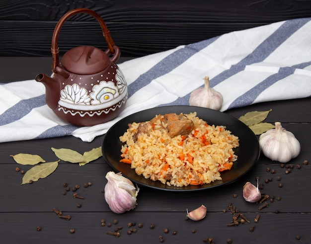 Traditional tasty pilaf with garlic and spices on black plate. kazakhstan national dish.