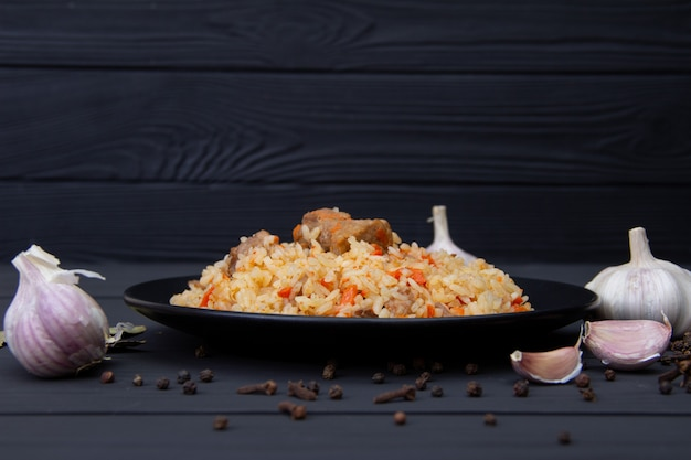 Traditional tasty pilaf with garlic and spices on black plate. uzbekistan national dish.