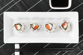 Traditional tasty sushi in white tray with sauce and chopsticks