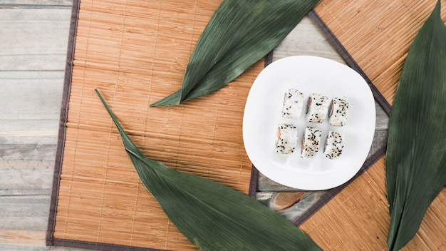 Traditional tasty sushi rolls in white plate with placemat and leaves on wooden table