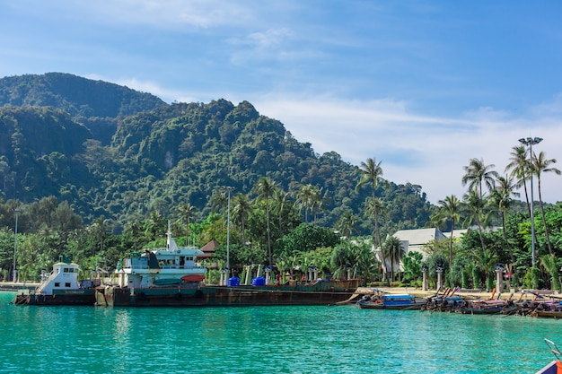 Traditional thai fishing boats wrapped with colored ribbons, against the backdrop of a tropical island,