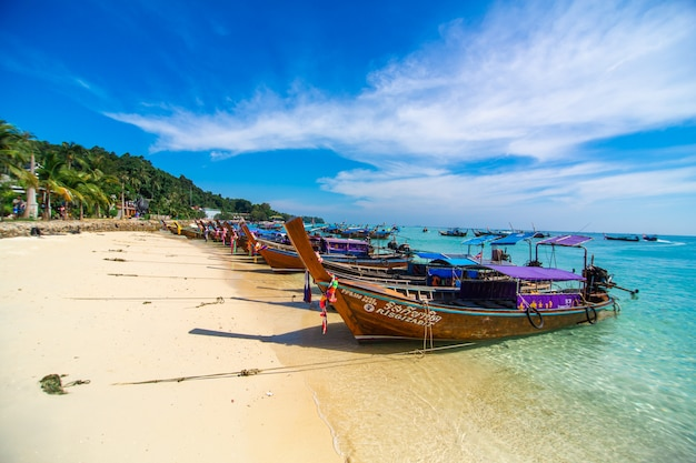 Traditional thai fishing wooden boats wrapped with colored ribbons. at sand coast of tropical island.