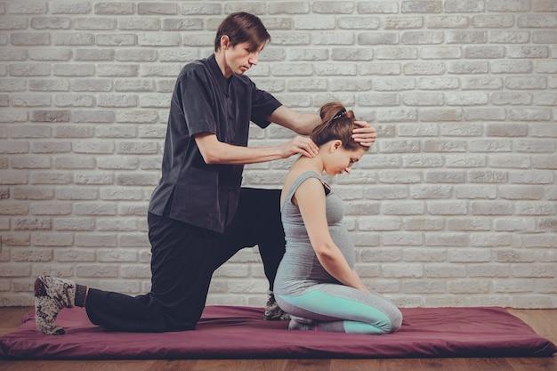 Традиционный тайский массаж беременной женщины, сидящей на коврике в студии йоги молодой белый массажист