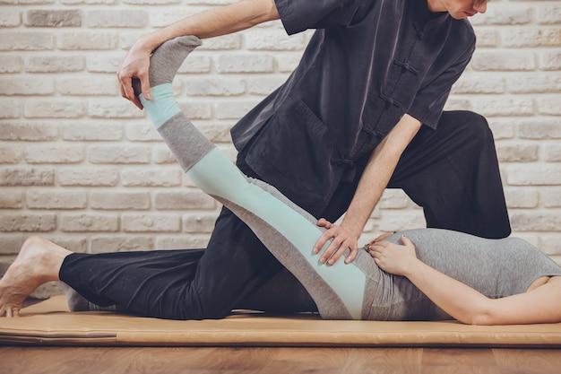 Традиционный тайский массаж беременной женщины, лежащей на коврике в студии йоги молодой белый массажист