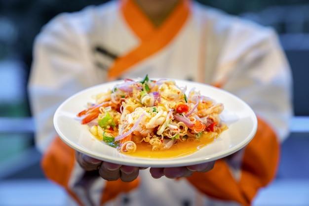 Традиционная тайская острая вермишель из лапши с морепродуктами, креветками, кальмарами и тайскими травами под рукой повара.