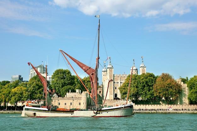 Традиционная темза баржа, плывущая по реке темзе с лондоном лондона на заднем плане
