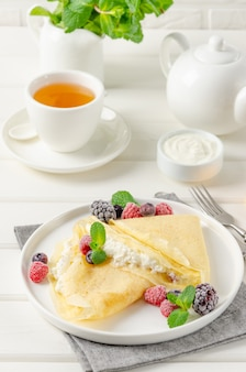 Traditional thin pancakes or crepes with cottage cheese and raisins with berries, honey and sour cream on a white wooden background. food for maslenitsa. copy space.