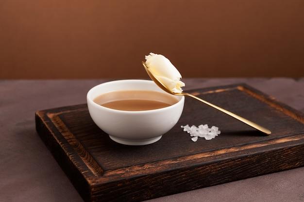 伝統的なチベットのバター茶または白いボウルのかき混ぜられたお茶。