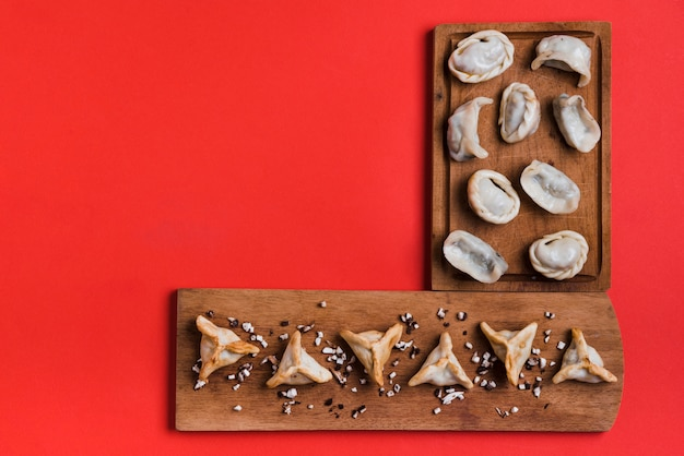 Traditional tibetan momo and dumpling in triangular shape on wooden tray against red backdrop