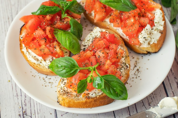 Traditional toasted italian tomato bruschetta with spice and basil on white plate