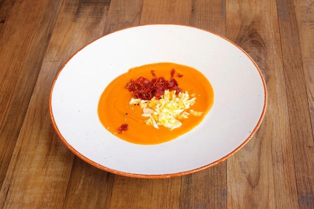 木製の背景にスペインからの伝統的なトマトスープ。