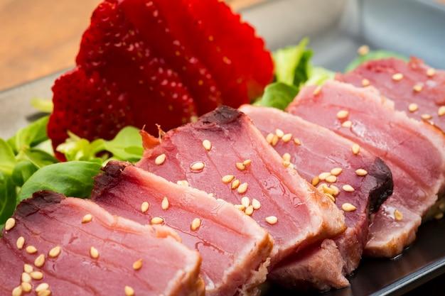 Традиционное блюдо татаки из тунца с клубникой, каноном и кунжутным соусом
