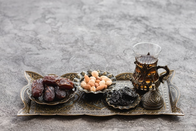 Traditional turkish arabic tea glasses; dates and nuts on metallic tray over the concrete backdrop