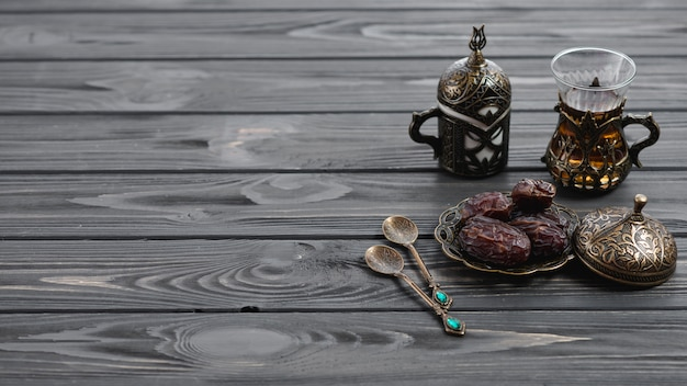 Traditional turkish arabic tea glasses and dried dates with spoons on wooden table
