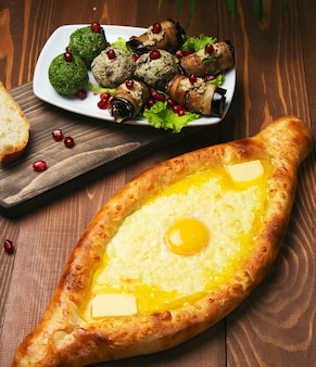 Traditional turkish baked dish pide. turkish pizza pide with cheese and egg with vegetable salad.