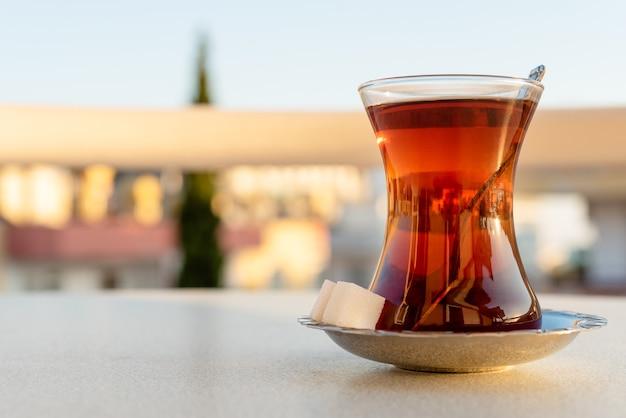 Традиционный турецкий черный чай в стеклянном стакане с блюдцем