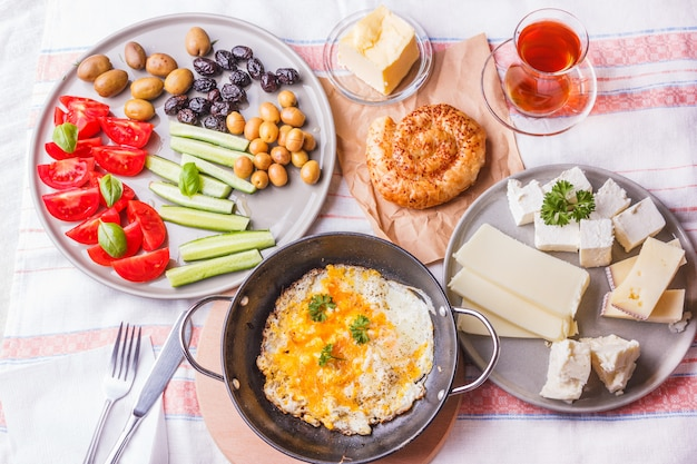 Traditional turkish breakfast - fried eggs, fresh vegetables, olives, cheese, cake and tea