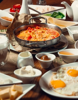 Traditional turkish breakfast with sunny side up eggs, nutella, egg dish menemen