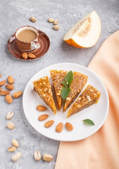 Traditional turkish candy cezerye from caramelised melon, pistachios on white plate and a cup of coffee