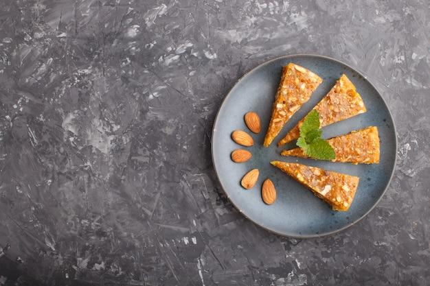 Традиционные турецкие конфеты cezerye из карамелизованной дыни, жареных грецких орехов, фундука, фисташек в синей керамической тарелке на черном бетонном фоне. вид сверху.