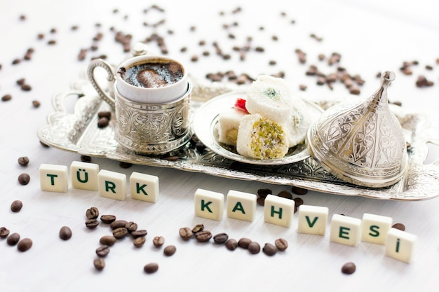 Traditional turkish coffee and sweets in silverware. lettering - turkish coffee - in turkish language