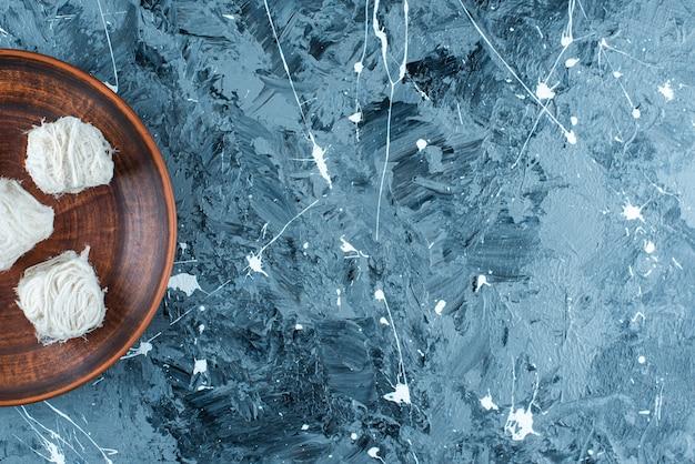 青いテーブルの上に、木の板の上に伝統的なトルコの綿菓子。