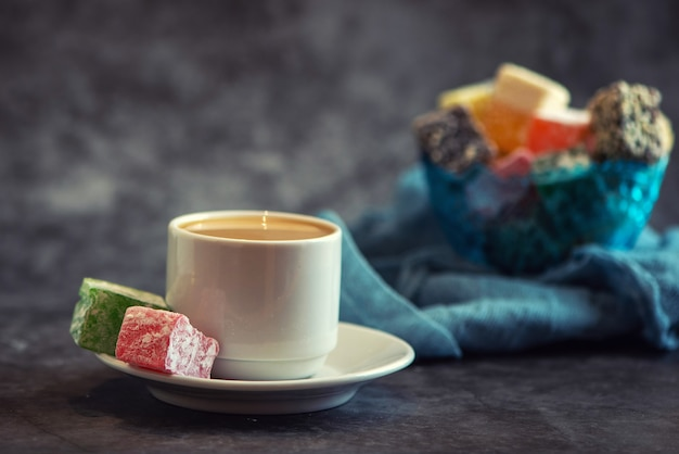 Traditional turkish delight and cup of coffee on grey background
