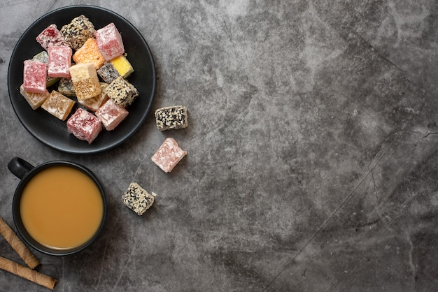 Traditional turkish delight and cup of coffee on grey. flat lay.