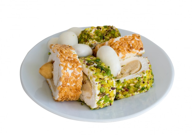 Традиционный лукум лукум на белой изолированной тарелке. сладкие роллы рахат лукум с ореховой пастой, фундуком, фисташками и кунжутом. рамадан сладости