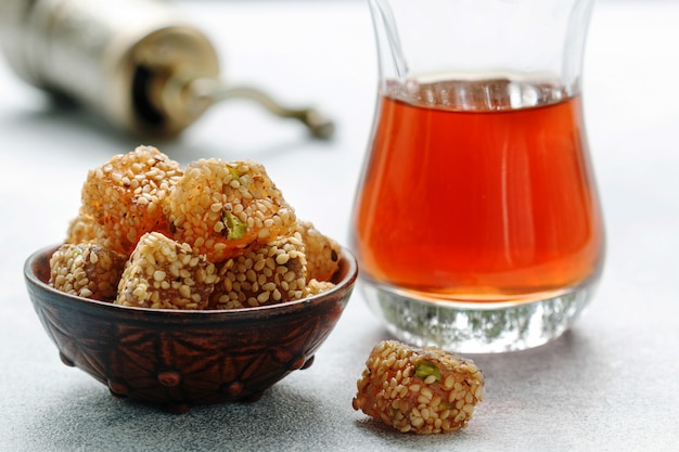Traditional turkish delight, lokum, oriental sweets with sesame and pistachios in a ceramic bowl on the table