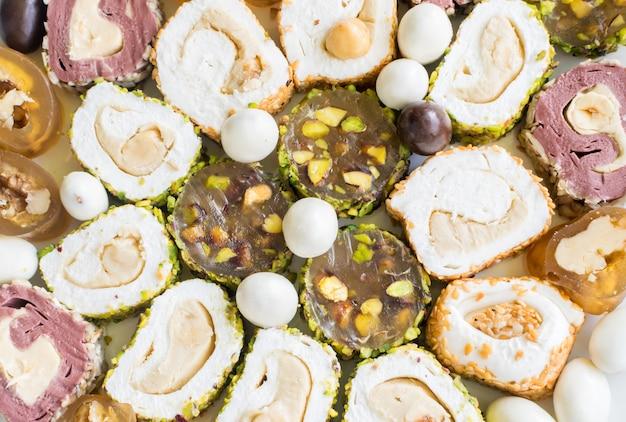 Традиционный лукум-лукум, вид сверху. сладкие роллы рахат лукум с ореховой пастой, фундуком, фисташками и кунжутом. рамадан сладости