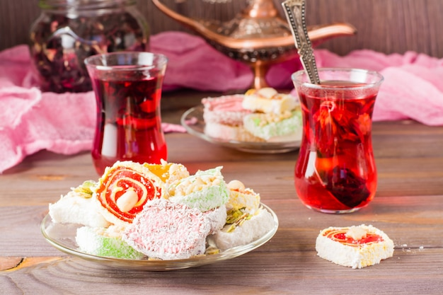 Traditional turkish delight on a plate and hot karkade in cups on a wooden table