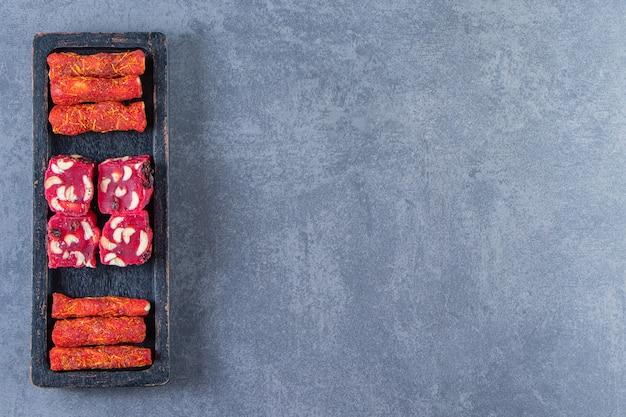 Традиционные лукумы на деревянной тарелке на мраморном фоне.