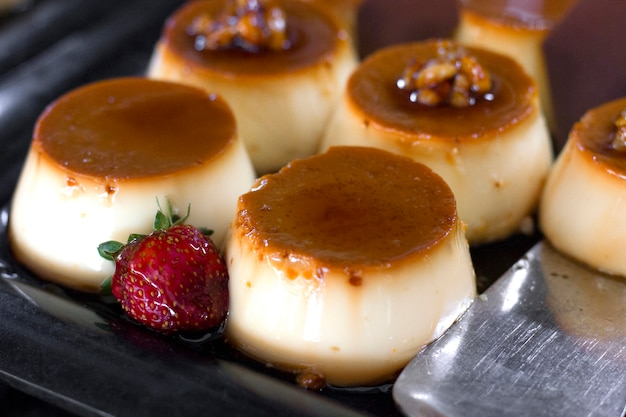 Traditional turkish dessert - cream caramel, decorated with fresh strawberries, on a black tray