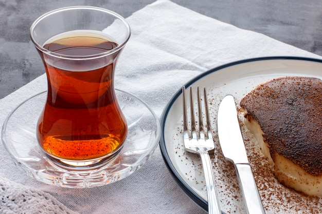 Traditional turkish dessert kazandibi with ground cinnamon and turkish tea