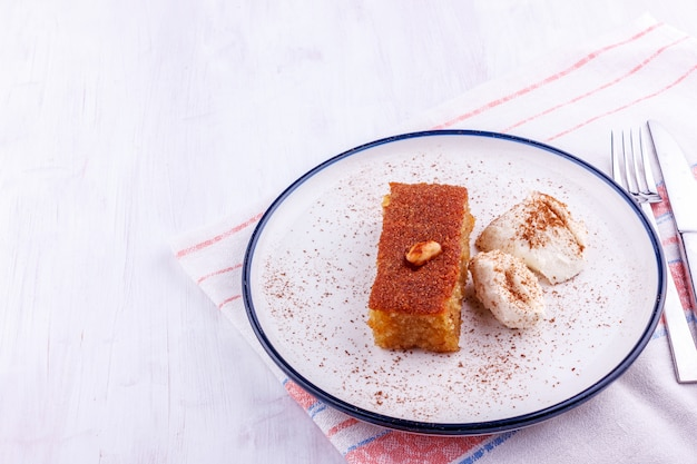 Traditional turkish dessert - sambali, sambaba or damascus with cream and cinnamon powder