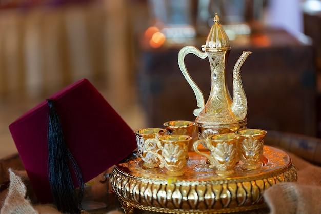 フェズと呼ばれる伝統的なトルコの帽子と東部のピッチャーがトレイと銅のグラスの上に立つ