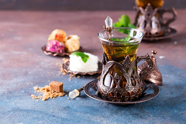 Traditional turkish tea with mint leaves and sweets in a traditional glass on concrete
