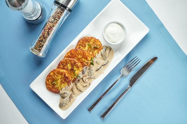 Традиционное украинское и белорусское блюдо - жареные картофельные оладьи (драники, деруны) со сметаной и белыми грибами, поданные в белой тарелке на синем столе.