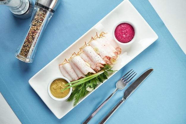 전통적인 우크라이나 전채-겨자, 양 고추 냉이 양파, 마늘을 곁들인 훈제 돼지 고기 라드 (살로, 베이컨), 파란색 테이블에 흰색 접시 제공