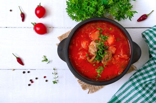 Traditional ukrainian borsch with young vegetables and meat in a black clay pot on a white wooden surface