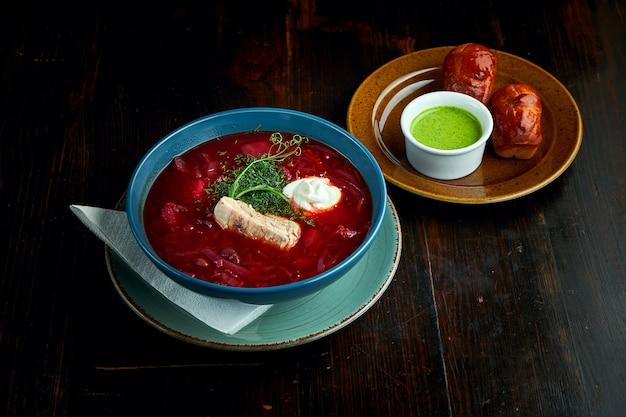 Традиционный украинский борщ с ребрами и сметаной, подается в голубой тарелке с пампушкой и ароматным маслом на темном фоне.