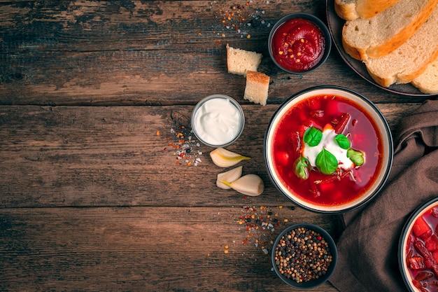 전통적인 우크라이나 요리. 부 끄 러운, 사 우 어 크림 및 복사를위한 공간을 가진 나무 배경에 마늘 borscht.