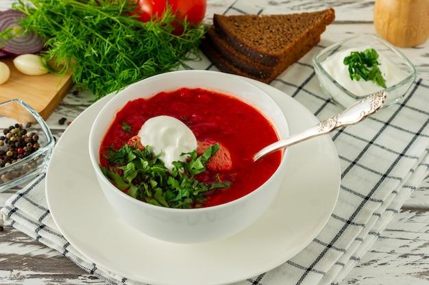 ニンニクとパンと伝統的なウクライナのロシアのボルシチ。白い木製のテーブルの上に赤いビートルートボルシチのボウル。ビートルートスープ。伝統的なスラブ料理。
