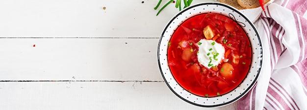 그릇에 흰 콩으로 전통적인 우크라이나어 러시아 보르시. 근대의 뿌리 수프. 흰색 테이블에 붉은 사탕 무우 루트 수프 borsch의 접시. 전통적인 우크라이나 음식 요리. 배너. 평면도