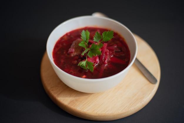 Традиционный украинский русский суп борщ свекольный суп в белой миске на деревянной доске